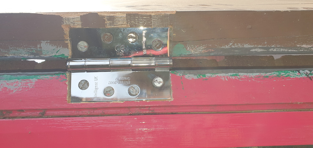Broken lock in a door with sheet metal plate. Hinges cut off to protect the metal plate from damage. Then hinges replaced.